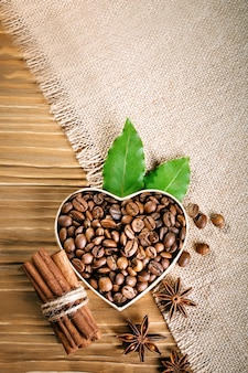 Fried coffee beans lie in the form of heart on wooden boards and burlap.