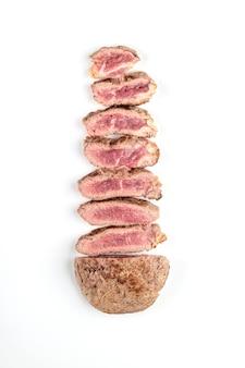튀긴 요리 쇠고기 스테이크는 하얀 접시에 조각으로 자른다. 평면도.