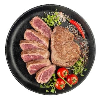 白地に隔離された鋳鉄製の鍋で、新鮮な野菜、トマト、ハーブ、スパイスを細かく切ったビーフステーキの炒め物。上面図。