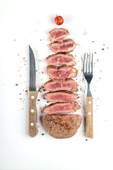 튀긴 요리된 쇠고기 스테이크는 흰색 배경에 향신료와 칼 붙이와 함께 조각으로 잘립니다. 평면도.