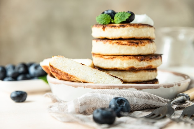 Fried cottage cheese pancakes or fritters with blueberry and sour cream on a plate