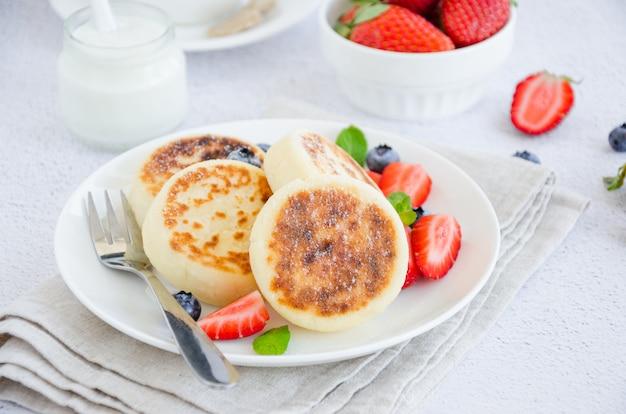 フライドカッテージチーズのパンケーキまたはサワークリームと白い皿に新鮮な果実とシロニキ。無グルテンの。ウクライナ料理とロシア料理の伝統的な朝食。水平、クローズアップ