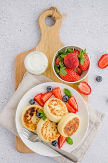 フライドカッテージチーズのパンケーキまたはサワークリームと白い皿に新鮮な果実とシロニキ。無グルテンの。ウクライナ料理とロシア料理の伝統的な朝食。垂直、トップビュー。