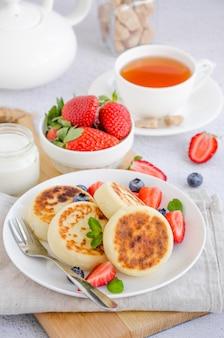 焼きたてのカッテージチーズのパンケーキまたはサワークリームと白い皿に新鮮な果実とシロニキ。無グルテンの。ウクライナ料理とロシア料理の伝統的な朝食。垂直