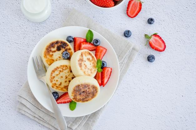 焼きたてのカッテージチーズのパンケーキまたはサワークリームと白い皿に新鮮な果実とsyrniki。無グルテンの。ウクライナ料理とロシア料理の伝統的な朝食。