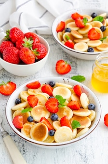 Жареные творожные оладьи со свежими ягодами на белой тарелке