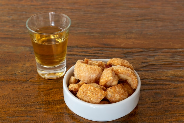 Fried cracklings in a white bowl and glass with cachaca typical dish of brazilian cuisine