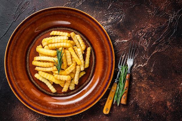 프라이드 크링클(fried crinkle) 프렌치 프라이 감자나 칩을 소박한 접시에 담습니다. 어두운 배경입니다. 평면도. 공간을 복사합니다.