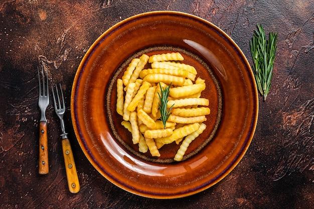 프라이드 크링클(fried crinkle) 프렌치 프라이 감자나 칩을 소박한 접시에 담습니다. 어두운 배경입니다. 평면도.