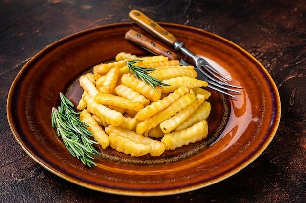 Fried crinkle french fries картофель или чипсы на деревенской тарелке