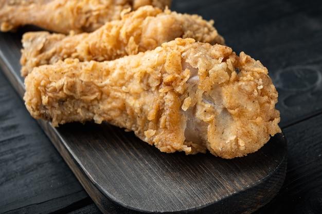 튀긴 바삭한 닭 다리, 검은 나무 테이블에 드럼 스틱 부분
