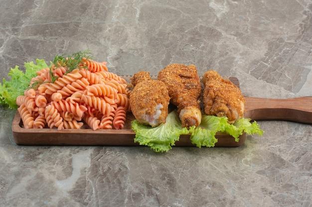 Pepite di pollo croccanti fritte con deliziosi maccheroni su tavola di legno.