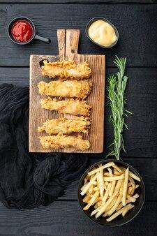 검은 나무 테이블에 튀긴 바삭한 치킨 줄무늬 부분