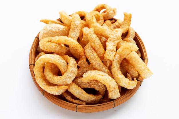 흰색 바탕에 대나무 바구니에 튀긴 바삭한 돼지 껍질.