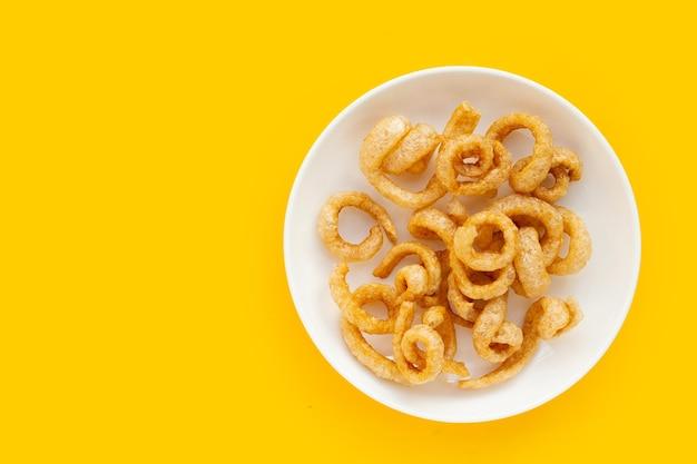 노란색 배경에 흰색 접시에 튀긴 바삭한 돼지 껍질.