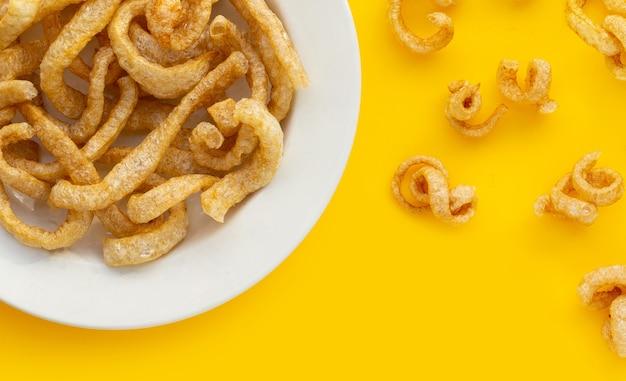 노란색 배경에 튀긴 바삭한 돼지 껍질입니다.