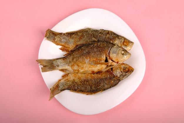 분홍색 배경에 흰색 접시에 황금 껍질과 튀긴 붕어 요리 생선.