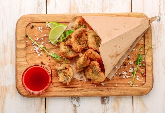 テーブルの上にカリカリのアンチョビを揚げ、サラダを葉します。用紙の背景。コーンフライの小魚を揚げ物の上でパンします。