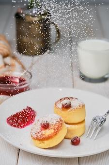 Жареные творожные оладьи - сырники, посыпанные сахарной пудрой на тарелке на белом деревянном столе.