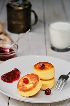 Жареные творожные оладьи - сырники на тарелке. вкусный завтрак на белом деревянном столе