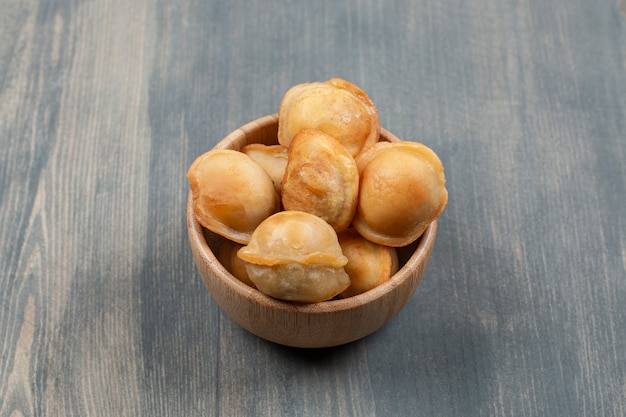 Жареные вкусные пельмени в деревянной миске