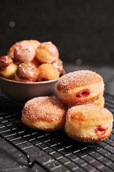 블랙 테이블에 설탕과 크림과 함께 튀긴 도넛