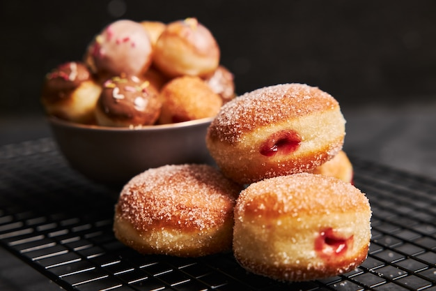 Fried donuts with sugar and cream on a black table