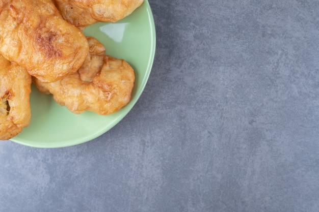 Bastoncino di pasta fritta sul piatto, sul marmo.