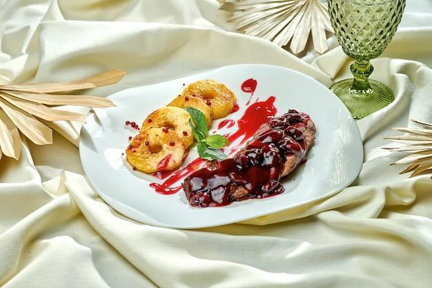 Жареная утиная грудка конфи с ягодным соусом и персиком в белой тарелке на скатерти