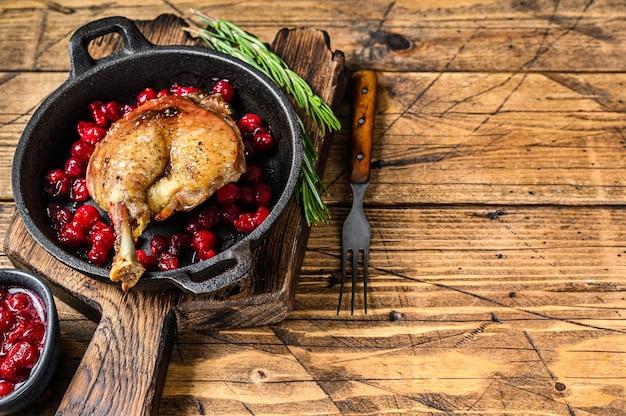 鍋にクランベリーソースをかけたアヒルの脚の炒め物。木製の背景。上面図。スペースをコピーします。