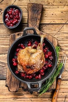 鍋にクランベリーソースをかけた鴨の脚のフライ