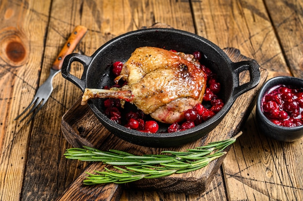 Fried duck leg with cranberrie sauce in a pan