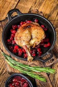 Fried duck leg with cranberrie sauce in a pan.