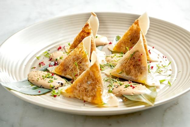 Жареные пельмени или японские гёдза в желтом соусе с помидорами черри и зеленым горошком, которые подаются в белой тарелке на мраморном столе. паназиатская кухня. еда в ресторане