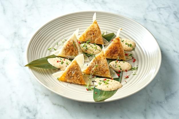 揚げ餃子または餃子の黄色いソース、チェリートマト、グリーンピースを、大理石のテーブルの白いプレートに盛り付けました。汎アジア料理。レストランの食べ物