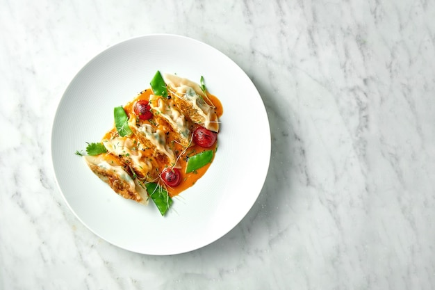 노란색 소스, 체리 토마토, 녹색 완두콩에 튀긴 만두 또는 일본식 만두가 대리석 테이블에 흰색 접시에 담겨 제공됩니다. 범 아시아 요리. 레스토랑 음식