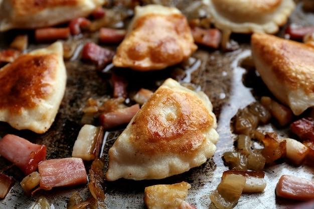 Жареные пельмени с луком и беконом на сковороде