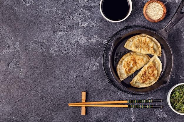 Жареные пельмени с соевым соусом и палочками для еды
