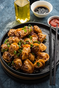 Fried dumplings with soy sauce with pepper and green onions. asian cuisine