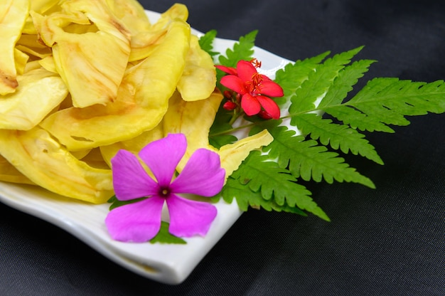 Fried durian with flowers and leaves in dish on table