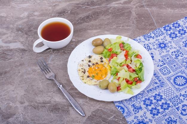 Жареное яйцо и нарезанный зеленый салат с чашкой чая.