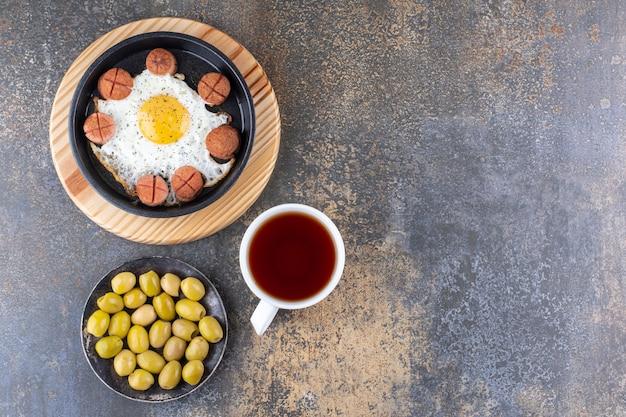 Жареные яйца и сосиски на сковороде, подаются с оливками и чаем