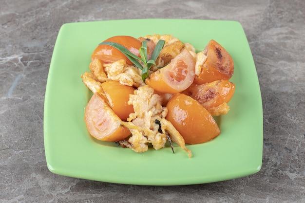 Жареные яйца и помидоры на зеленой тарелке.