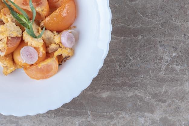 Жареные яйца и помидоры на белой тарелке.