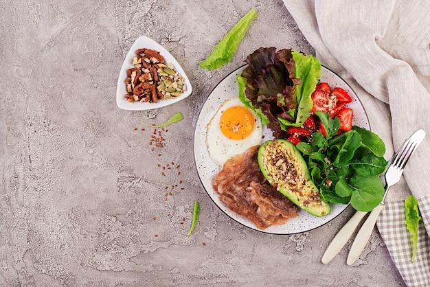 Fried egg, bacon, avocado, arugula and strawberries