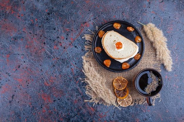 Жареное яйцо между двумя ломтиками хлеба на доске рядом с чашкой чая на синем фоне.