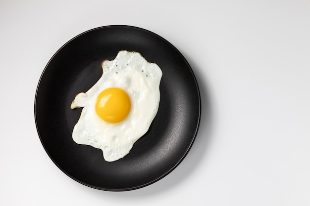 Fried egg on a black plate. isolated on white background.