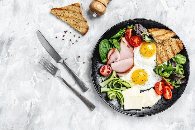 Fried egg ham tomatoes for healthy breakfast. english breakfast toast, egg, bacon and vegetables. banner, menu recipe place for text, top view.