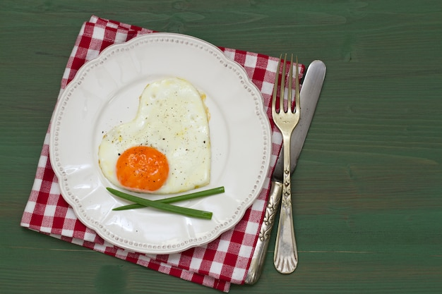 Fried egg heart with onion on white plate