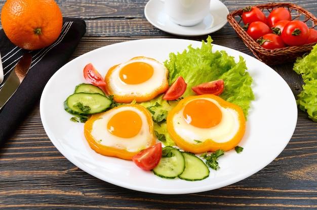 Жареное яйцо в кругу сладкого перца на белой тарелке со свежими овощами, чашкой кофе, свежими апельсинами на деревянном фоне.
